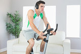 Stern handsome man training on exercise bike listening to music