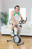 Cheerful handsome man training on exercise bike listening to music