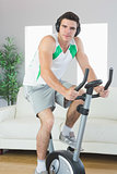 Content handsome man training on exercise bike listening to music