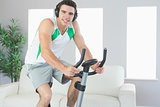 Smiling handsome man training on exercise bike listening to music