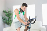 Sporty handsome man training on exercise bike using tablet