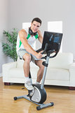 Smiling handsome man training on exercise bike using laptop