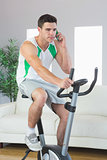 Stern handsome man training on exercise bike phoning