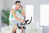Serious handsome man training on exercise bike phoning
