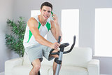 Smiling handsome man training on exercise bike phoning