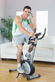 Cheerful handsome man training on exercise bike phoning