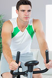 Unsmiling handsome man training on exercise bike