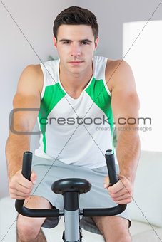 Stern handsome man training on exercise bike
