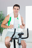 Cheerful handsome man training on exercise bike