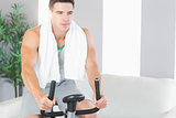 Determined handsome man exercising on exercise bike