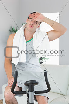 Tired handsome man exercising on exercise bike