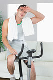 Exhausted handsome man training on exercise bike