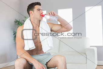 Attractive sporty man drinking from water bottle