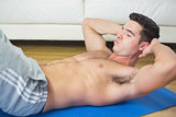 Frowning handsome man doing sit ups