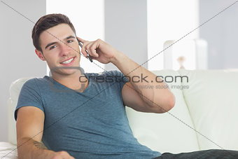 Portrait of cheerful handsome man relaxing on couch phoning