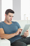Peaceful handsome man relaxing on couch using tablet