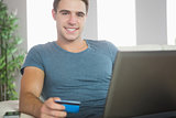 Cheerful handsome man relaxing on couch using laptop shopping online