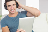 Cheerful handsome man using tablet listening to music