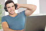 Cheerful handsome man using laptop listening to music
