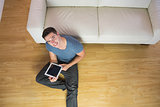 Overhead view of handsome smiling man using tablet