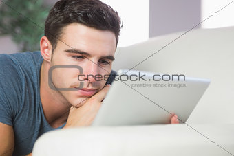 Focused handsome man lying on couch using tablet