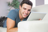 Cheerful attractive man lying on couch using tablet