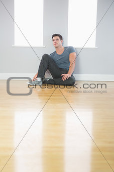 Thoughtful handsome man leaning against wall sitting on the floor