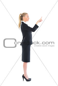Profile view of young business woman pointing