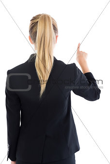 Rear view of ponytailed blonde businesswoman pointing