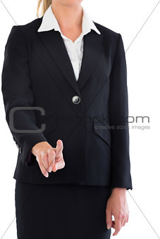 Mid section of blonde businesswoman pointing at camera