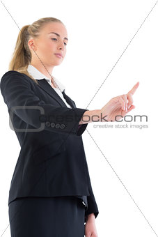 Low angle view of young businesswoman pointing upwards