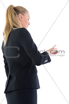 Ponytailed blonde business woman pointing upwards