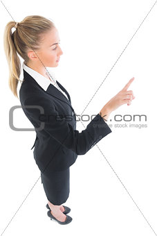 High angle profile view of young businesswoman pointing upwards