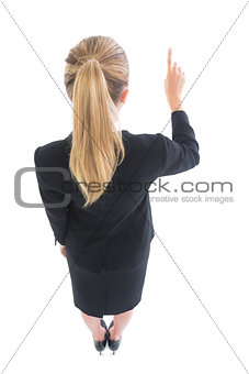 High angle rear view of blonde business woman pointing
