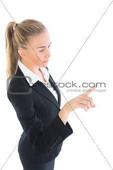 Ponytailed young business woman pointing