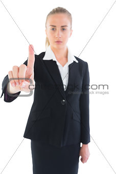 Serious attractive businesswoman pointing upwards