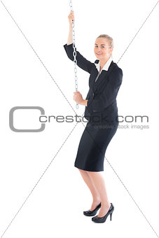 Blonde businesswoman climbing a chain
