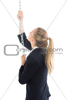 Attractive blonde businesswoman climbing a silver chain
