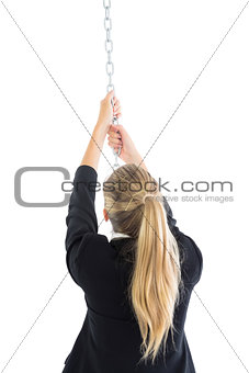 Rear view of blonde businesswoman pulling a chain