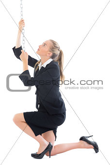 Focused young businesswoman pulling a chain