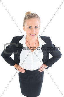 Amused young businesswoman posing with hands on hips
