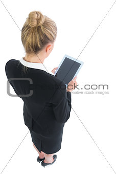 Blonde young businesswoman making use of her tablet