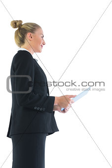 Low angle profile view of smart businesswoman holding her tablet
