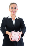 Attractive cheerful businesswoman showing a piggy bank