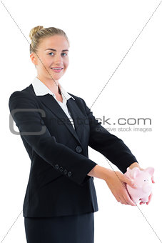 Attractive young businesswoman holding a piggy bank