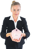 Cute businesswoman holding a piggy bank