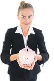 Cute businesswoman holding a piggy bank