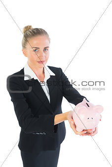 Attractive chic businesswoman presenting a piggy bank