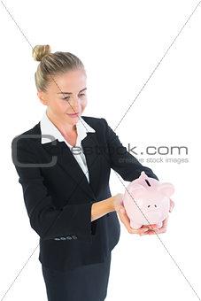 Beautiful modern businesswoman holding a piggy bank