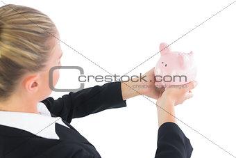Blonde cute businesswoman holding a piggy bank